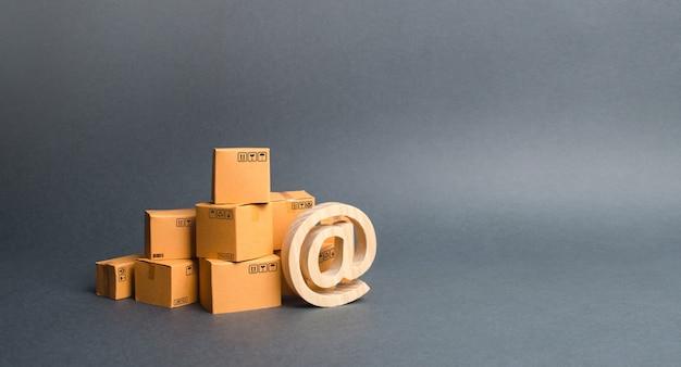 Куча картонных коробок и символ рекламы at. покупки онлайн. электронная коммерция. продажа товаров