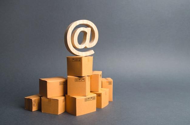 Рекламный символ электронной коммерции at находится на стопке картонных коробок. электронная коммерция