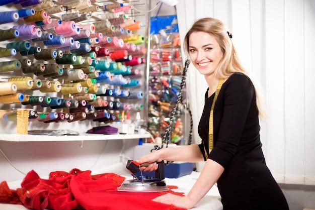Ателье дизайн-студия по пошиву одежды. дизайнер пропаривает ткань перед тем, как разрезать кусочки.