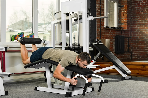 Atheletic man swing the abdominal muscles in gym