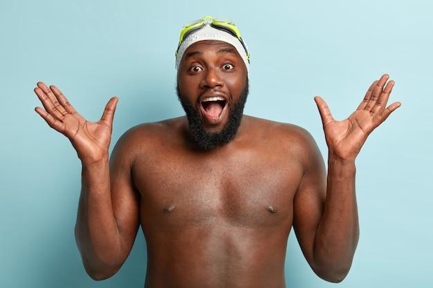 太い毛を持ったathelitcの浅黒い肌の男水泳選手は、手を上げ、青い壁に向かって裸でポーズをとり、水泳帽とゴーグルを着用し、体操のトレーニングを受け、前向きな感情から叫びます。