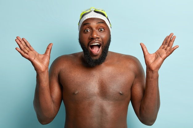 Athelitc dark skinned man swimmer with thick bristle, raises hands, poses naked against blue wall, wears swimming cap and goggles, has gymnastic training, exclaims from positive emotions.