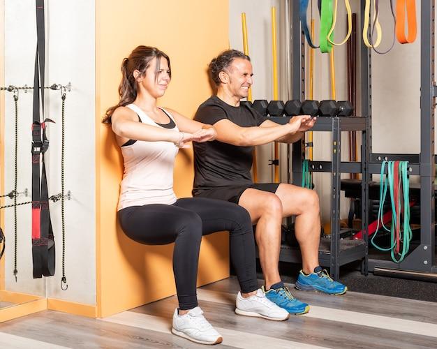 체육관에서 벽에 기대어 스쿼트를 하는 athete 사람들. 체육관의 개념입니다.