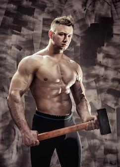 Спортсмен и молот. парень с хорошей мускулатурой, тренер по бодибилдингу держит большой металлический молот