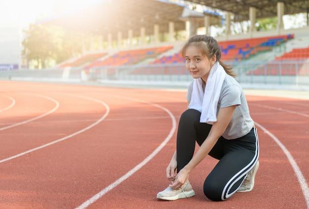 ジョギングトラック、スポーツ、健康概念の準備ランニングシューズをしようとしているアスリートアジアの女の子