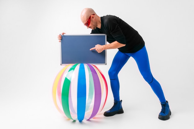 Athlete bald man in red sunglasses and blue sportive tights standing near beach ball and showing his hand to nameplate. sport motivation concept