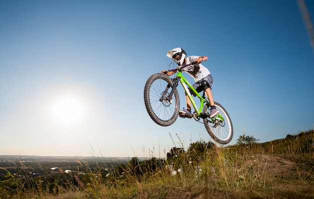 Athlete biker jumps on a mountain bike on the hill in the evening