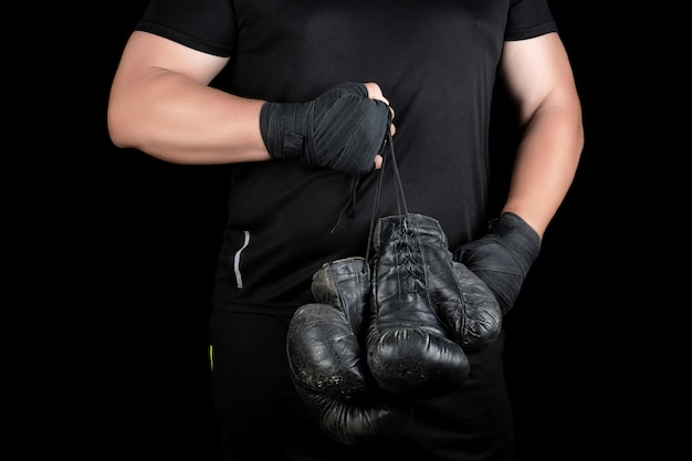 Athlete in black clothes holds very old vintage leather black boxing gloves