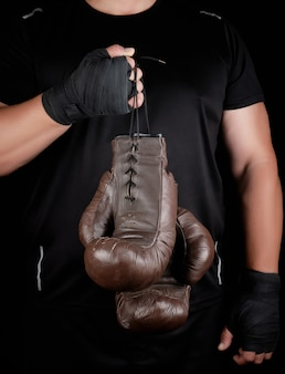 Athlete in black clothes holds very old vintage leather brown boxing gloves