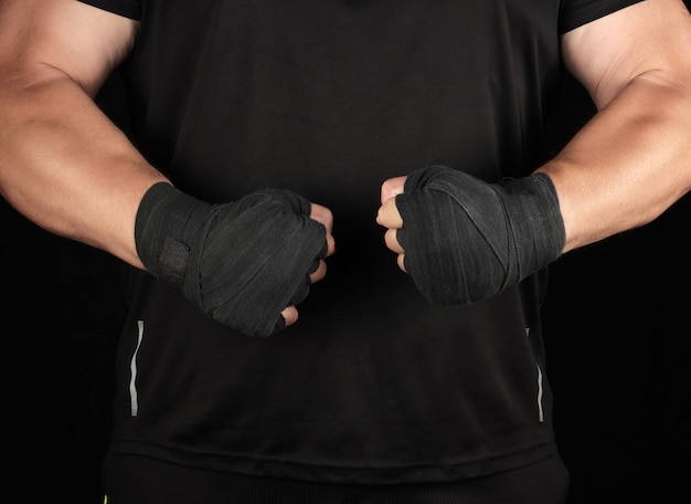 Athlete in black uniform is standing in a rack with strained muscles, his hands are wrapped in a black textile bandage
