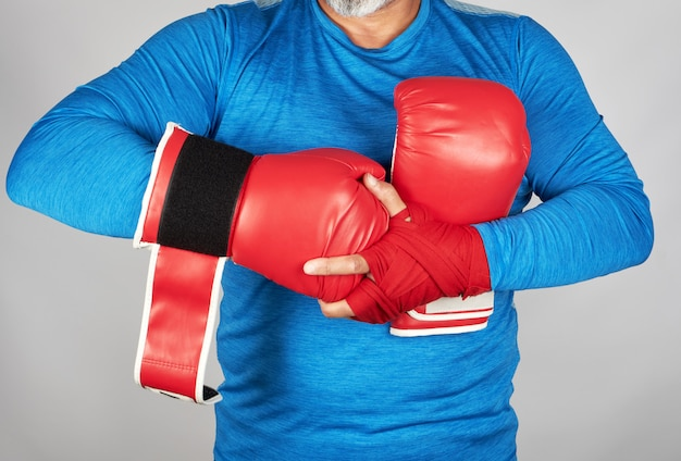 Athlete in blue clothes, hands are rewound with red textile bandage