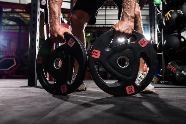 Athlete bodybuilder holding dumbbell discs in hand