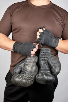 Athlete in brown clothes holds very old vintage leather black boxing gloves