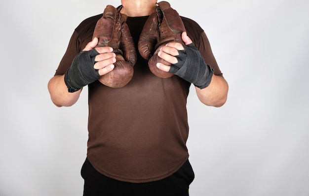 Athlete in brown clothes holds very old vintage leather boxing gloves