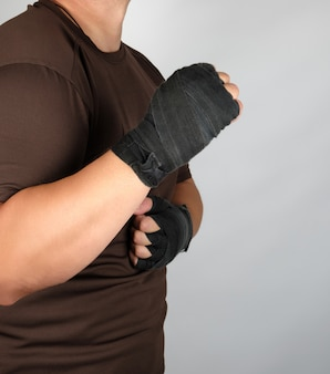 Athlete in brown clothes with bandaged hands black textile sports bandage