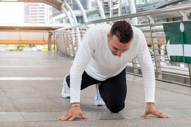 Athlete caucasian man in running start pose on the city street.