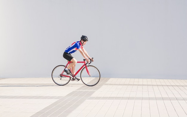 Athlete cyclist rides on a bike on a white light wall