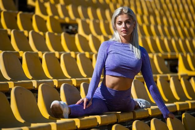 운동 선수는 스트레칭 스포츠 운동을 합니다. 트레이너 또는 코치 훈련. 완벽한 신체 유연성. 건강하고 스포티합니다. 운동복에 섹시 한 피트 니스 여자입니다. 운동 여자는 경기장 트리뷴에 분할에 앉아 있다.