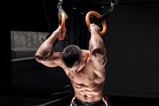 Спортсмен делает разминку на гимнастических кольцах.