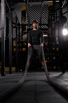 Athlete doing battle ropes exercise at cross fit gym. motivation sport concept. male engaged in intense workout raining. copy space.