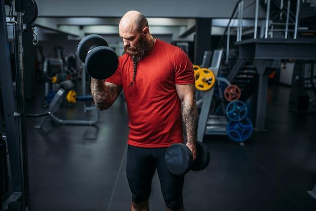 Спортсмен делает упражнения с гантелями в тренажерном зале