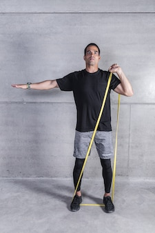 Athlete doing exercise with rubber elastic band