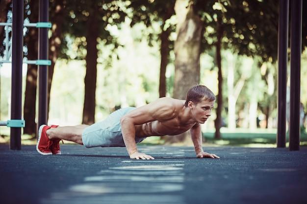 Athlete doing exercises at stadium at park