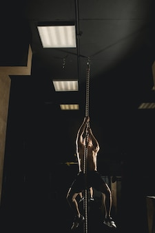 Athlete doing fitness rope climb exercise in fitness gym workout