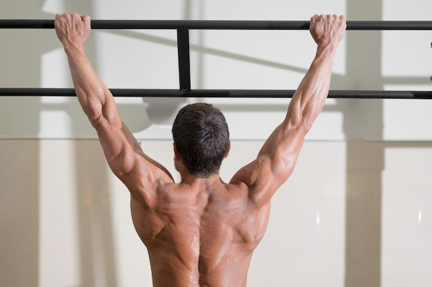 Athlete doing pullups at the gym handsome man doing functional training