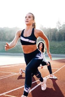 운동 선수는 개인 트레이너와 함께 경기장에서 출발한 다음 앞으로 돌진하여 운동합니다.