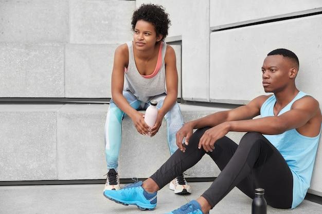 アスリートの女性と男性のランナーが階段に座り、深く考え、カジュアルな服を着て、スポーツウェアからコーヒーを飲み、ジョギング後に疲れた休息を感じます。人、モチベーション、フィットネスの概念