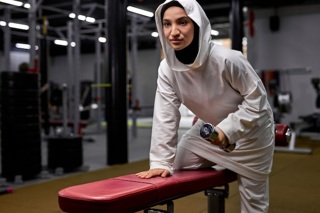 현대 피트니스 센터에서 아령으로 히잡 훈련을하는 선수 여성, 젊은 무슬림 여성은 에너지와 힘이 가득합니다. 동기 부여, 건강한 라이프 스타일 및 스포츠 컨셉