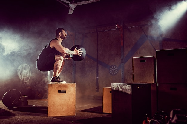 Athlete gave exercise. jumping on the box. phase touchdown. gym shots in the dark tone. smoke in gym.