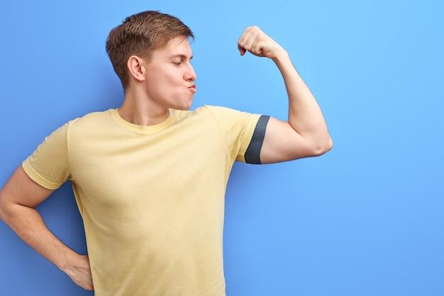 腕の筋肉、彼の強さ、青い背景の上に孤立したポーズをとって、筋肉にキスをしているカジュアルなtシャツの男性を示す運動選手の男。ボディービル、スポーツ、トレーニングの概念