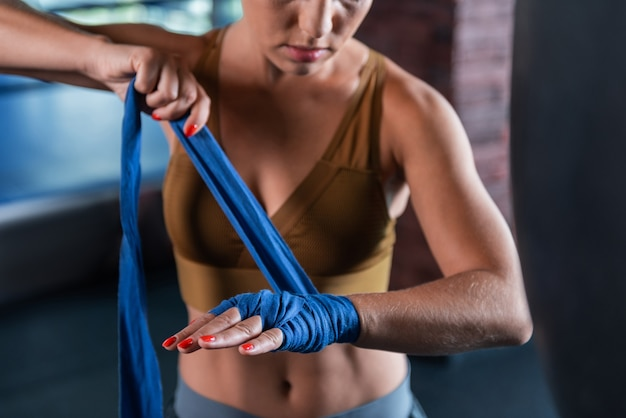 선수 손. 긴 파란색 손목 랩에서 압 연하는 밝은 빨간색 네일 아트와 여성 운동 선수의 손을 가까이