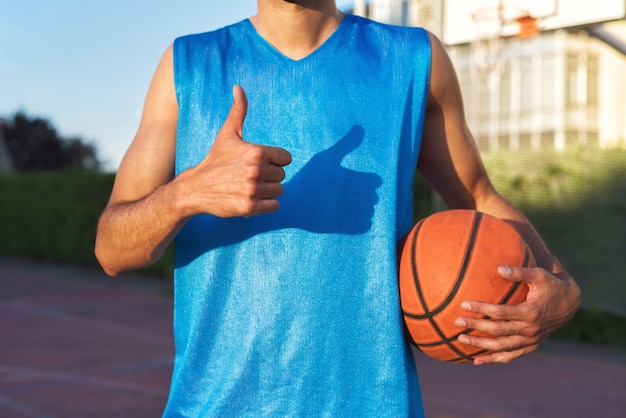 Athlete holding basketball ball with thumb up