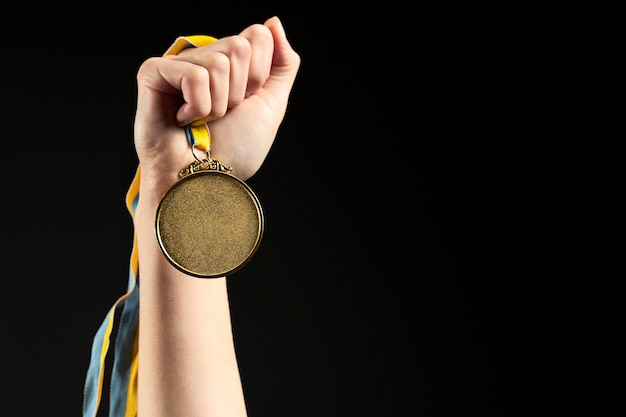 Спортсмен, держащий золотую медаль крупным планом