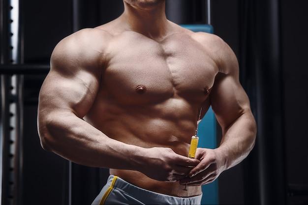 アスリートは、裸の胴体を持った注射器と注射器を目の前に持っています。スポーツと予防接種医学の概念