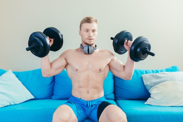 Athlete at home doing fitness uses dumbbells