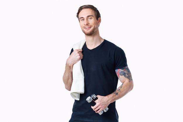 彼の腕とタオルの白い背景の入れ墨のダンベルと黒のtシャツの運動選手