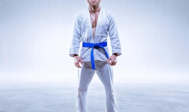青い帯の着物姿の選手が明るい背景に立っています。空手と柔道の概念。ミクストメディア