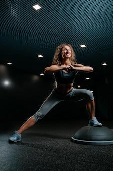 검은색 체육관의 선수는 깊은 근육을 위한 균형 플랫폼에서 스쿼트를 하는 피트니스에 종사하고 있습니다.