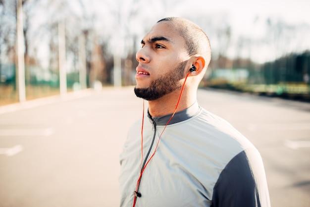 公園でジョギングする前にヘッドフォンでアスリート。朝のフィットネストレーニングのジョガー。スポーツウェアのランナー、屋外でのフィットネストレーニング