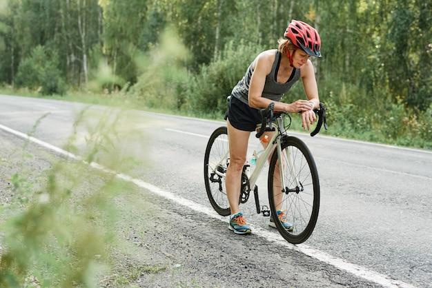 시골길에서 자전거를 타기 전에 헬멧을 쓴 선수가 피트니스 팔찌를 확인하고 있다