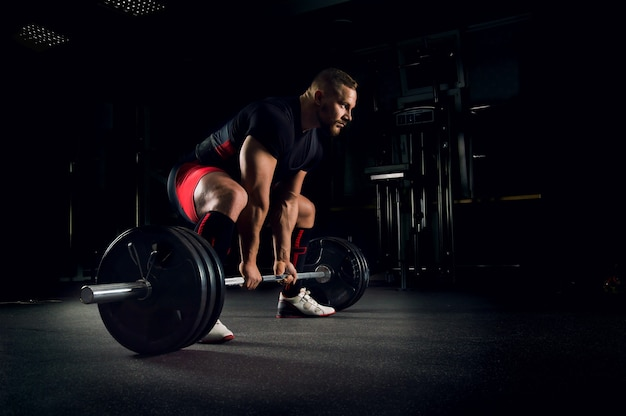 Спортсмен в тренажерном зале готовится к выполнению упражнения, называемого становой тягой.