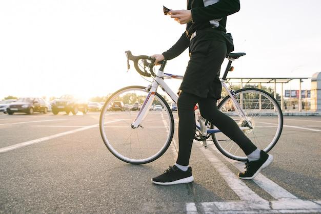 アスリートは、白い自転車で街を歩くスポーツウェアのサイクリストです。