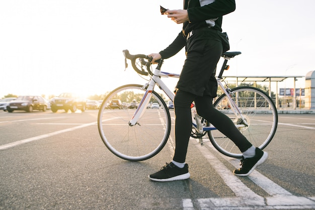 Athlete is a cyclist in sports wear walking around the city with a white bike.