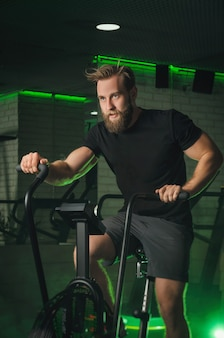 The athlete is engaged in the gym on the airbike