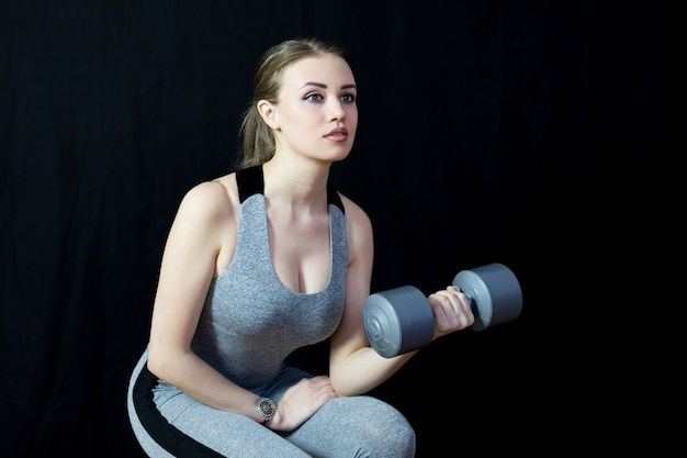 The athlete is engaged with heavy dumbbells on black.