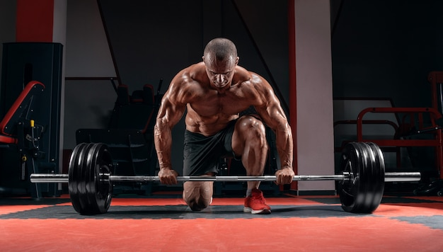 Athlete is standing on his knee and near the bar in the gym and is preparing to make a deadlift.